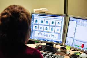 A woman analysing the digital scan of fingerprints.